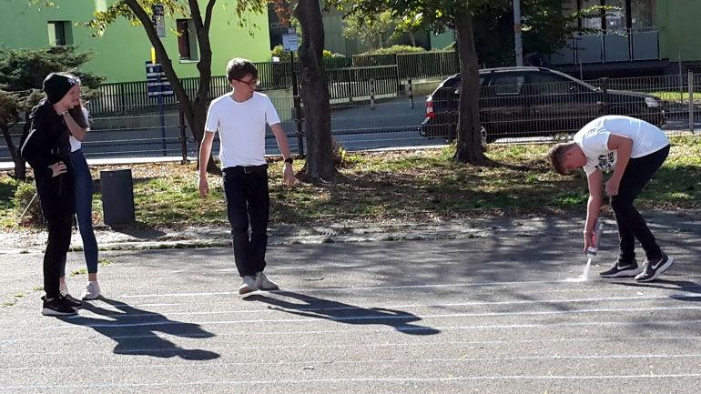 Schüler zeichen Koordinatensystem auf Schulhof